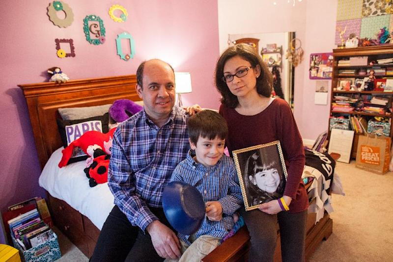 Mark Miller, left, Ellyn Miller, right, and their son Jake, center, pose for a portrait in their daughter, Gabriella's bedroom at their home in Leesburg, Va., on Wednesday, March 12, 2014. The Senate passed a bill, named for Gabriella, Tuesday that directs $126 million over the coming decade for childhood cancer research. (AP Photo/Zach Gibson)