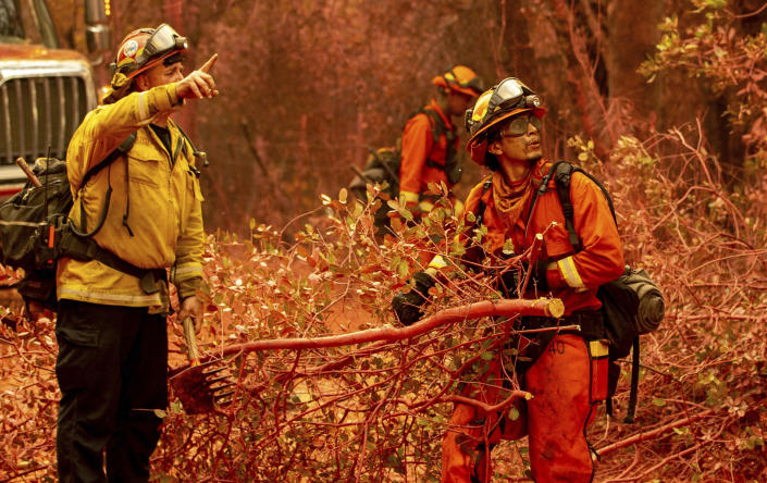 Inmate firefighters clear brush while battling the Fawn Fire burning north of Redding in Shasta County, Calif., on Thursday, Sep. 23, 2021. (AP Photo/Ethan Swope)