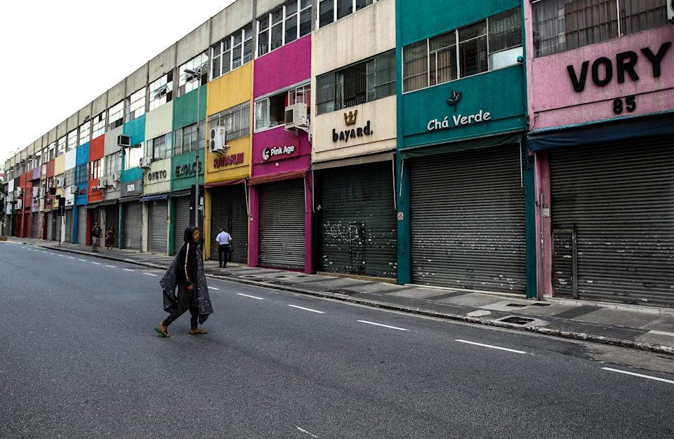 SAO PAULO, BRAZIL - MARCH 08: A homeless person walks by shuttered shops in downtown during the first business day after the state of Sao Paulo declared the most restrictive