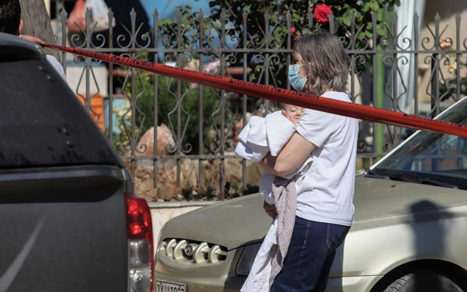 A young baby is removed away from the property in Glyka Nera in the outskirts of Athens - John Liakos/Intime News/Athena Pictures/Athena Picture Agency Ltd