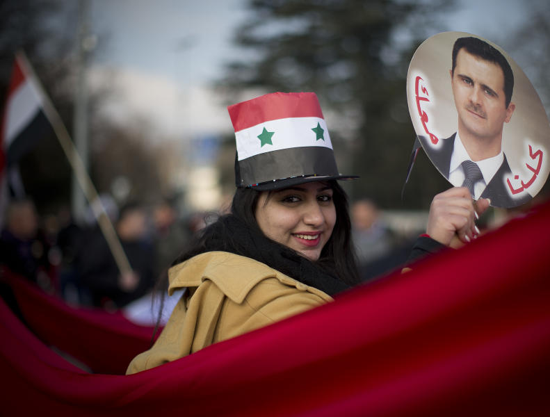 A Syrian demonstrator holds up a picture of Syrian President Assad as she shouts pro-government slogans during a demonstration outside the United Nations headquarters in Geneva, Switzerland, Friday Jan. 31, 2014. Arabic reading on the picture says 'we are all with you'. The first face-to-face meetings between Syria's warring sides in three years were wrapping up Friday, with a patient U.N. mediator struggling to build enough momentum for a more constructive second round to break through the deadly impasse. (AP Photo/Anja Niedringhaus)
