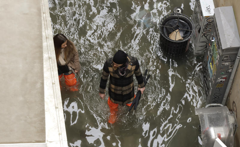 A couple walk in a flooded street of Venice, Italy, Sunday, Nov. 17, 2019. Venetians are bracing for the prospect of another exceptional tide in a season that is setting new records. Officials are forecasting a 1.6 meter (5 feet, 2 inches) surge of water Sunday through the lagoon city. (AP Photo/Luca Bruno)