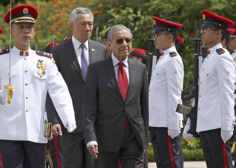 Malaysia's Prime Minister Mahathir Mohamad, center, inspects an honor guard with Singapore's Prime Minister Lee Hsien Loong, center left, during a visit at the Istana in Singapore, Monday, Nov. 12, 2018. (Feline Lim/Pool Photo via AP)