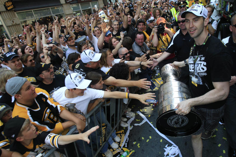 Boston Bruins captain Zdeno Chara carries the Stanley Cup as fans reach to touch the trophy during a rally in celebration of their NHL hockey Stanley Cup playoff victory in Boston., Saturday, June 18, 2011.  (AP Photo/Charles Krupa)