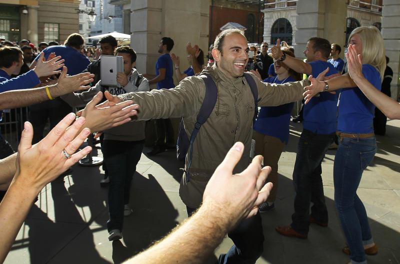 Customers are welcomed by Apple employees outside the Apple Store  in Covent Garden, as they arrive to buy the new iPhone 4S, which went on sale in London,  Friday, Oct. 14, 2011. (AP Photo/Kirsty Wigglesworth)