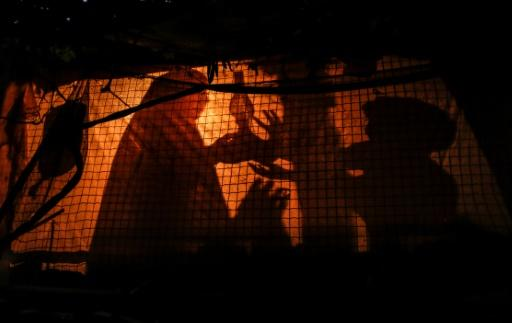 A Palestinian woman uses a gas lamp during a power cut in an impoverished area of the Khan Yunis refugee camp in southern Gaza on July 29, 2018