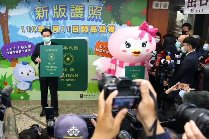 Taiwan's Foreign Minister Joseph Wu takes photos with a sample of the new Taiwan passport in Taipei