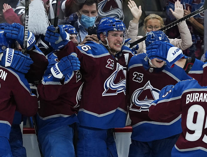 Colorado Avalanche right wing Mikko Rantanen, center, is congratulated by teammates after scoring in overtime against the Vegas Golden Knights during Game 2 of an NHL hockey Stanley Cup second-round playoff series Wednesday, June 2, 2021, in Denver. (AP Photo/Jack Dempsey)