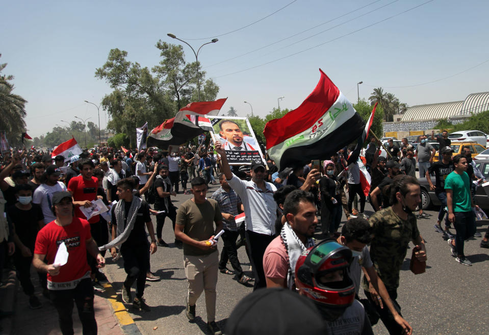 Anti-government protesters chant slogans as they hold posters of slain activist Ehab Wazni outside the Green Zone area which houses the seat of the country's government and foreign embassies, in Baghdad, Iraq, Tuesday, May 25, 2021. Hundreds of Iraqi protesters have taken to the streets of Baghdad to decry a recent spike in assassinations targeting outspoken activists and journalists. (AP Photo/Khalid Mohammed)