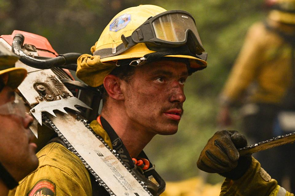 Firefighter hand crews put out hot spots near rustic mountain cabin homes on a hillside at the Dixie Fire, in Twain, California on July 26, 2021. - After battling increasingly large and deadly wildfires non-stop for weeks, and with no respite in sight, firefighters in California are admitting they are burnt out.