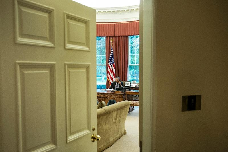 US President Barack Obama speaks on the phone in the Oval Office of the White House (AFP Photo/BRENDAN SMIALOWSKI)