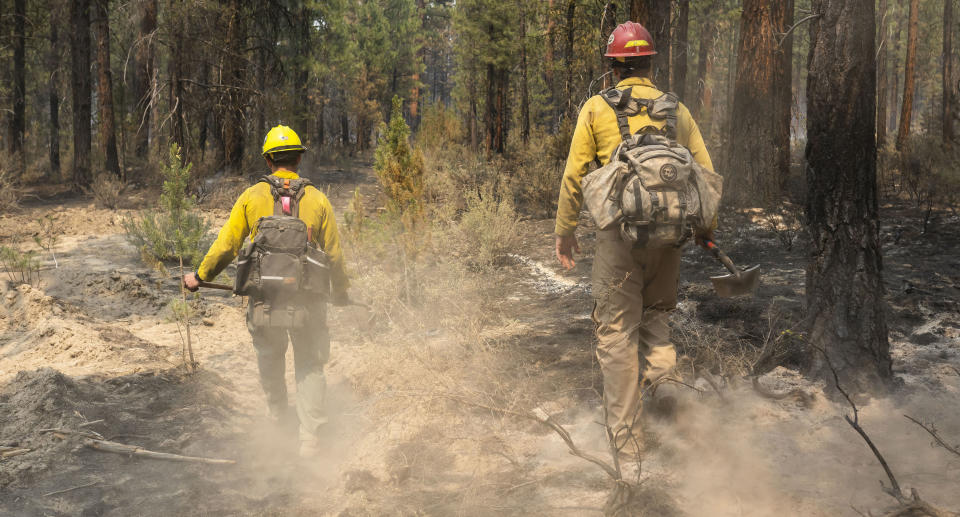 Firefighters Garret Suza, right, and Cameron Taylor, with the Chiloquin Forest Service, search for hot spots on the northeast side of the Bootleg Fire. Source: AP