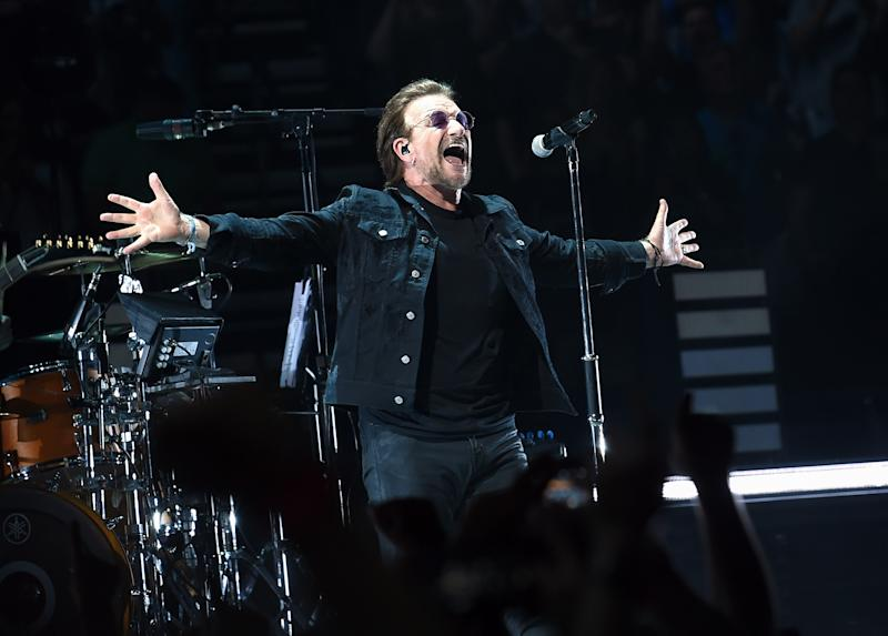 Bono from U2 performs in black outfit on stage