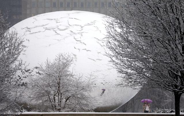 """Fresh snow covers Anish Kapoor's sculpture """"Cloud Gate"""" and gives it the appearance of a cracked egg as a lone pedestrian walks around the stainless steel attraction in Chicago's Millennium Park, as a winter storm of rain and snow begins Tuesday, Feb. 26, 2013. Forecasters expect the storm to leave behind three to six inches of snow in the greater Chicago area. (AP Photo/Charles Rex Arbogast)"""