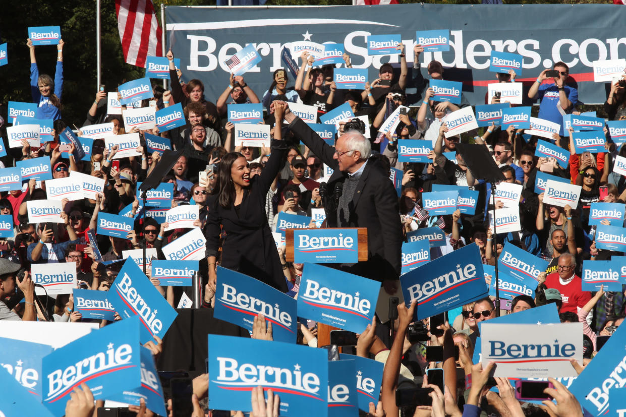 Rep. Alexandria Ocasio-Cortez clasps hands with Sen. Bernie Sanders after introducing Sanders during the rally on Saturday. (Photo: AP/Mary Altaffer)