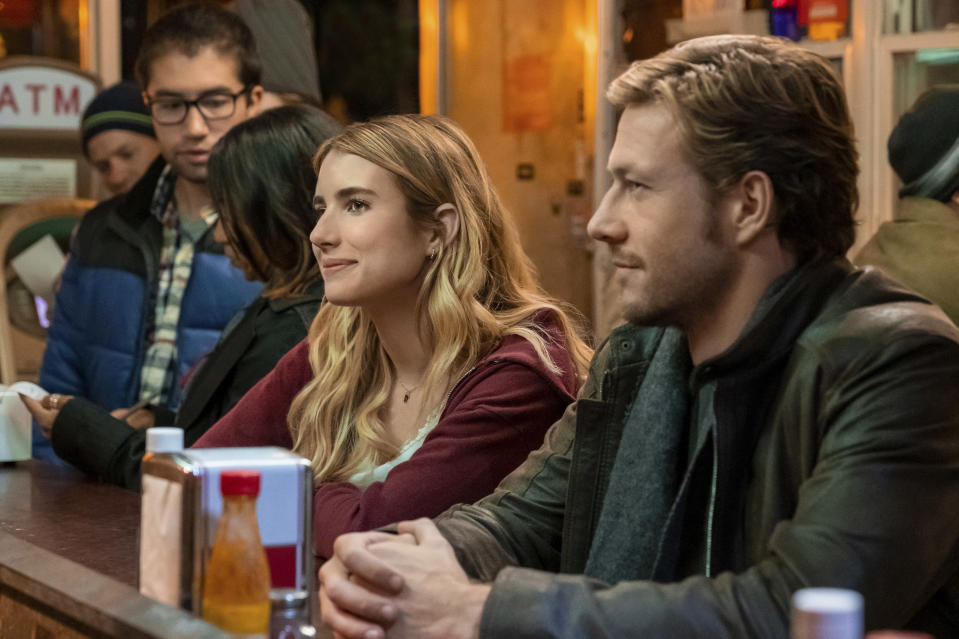 """This image released by Netflix shows Emma Roberts and Luke Bracey, right, in a scene from """"Holidate."""" (Steve Dietl/Netflix via AP)"""