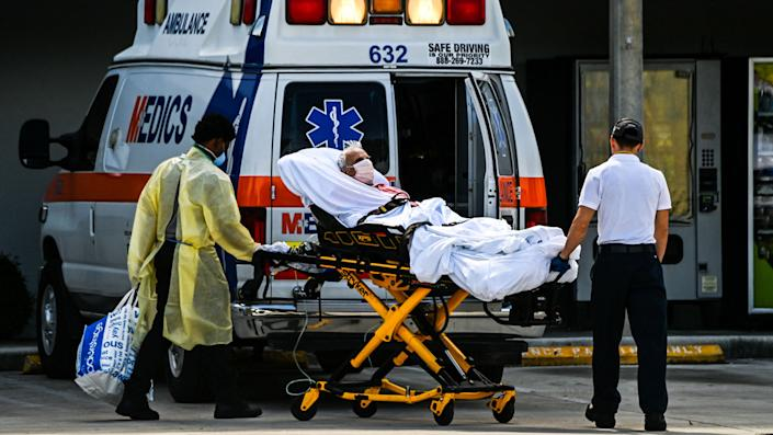 Medics transfer a patient on a stretcher from an ambulance outside of Emergency at Coral Gables Hospital where Coronavirus patients are treated in Coral Gables near Miami, on August 16, 2021. (Chandan Khanna/AFP via Getty Images)