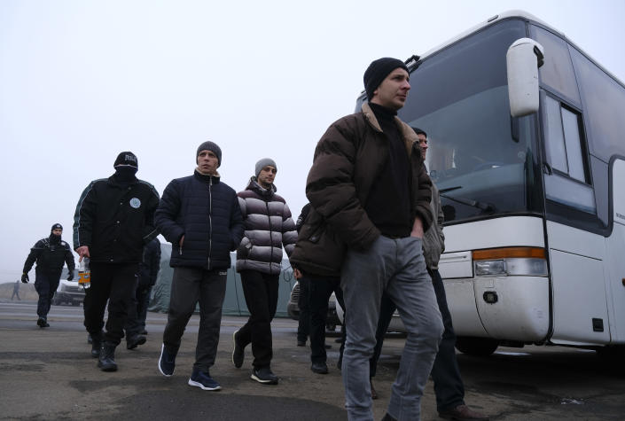 Pro-Russian prisoners walk before a prisoner exchange during a prisoner exchange between Ukrainian and pro-Russian rebels sides, near the Maiorske checkpoint, Donetsk area, Ukraine, Sunday, Dec. 29, 2019. Ukrainian forces and Russia-backed rebels in the east have begun exchanging prisoners in a move aimed at ending their five-year-long war. (Yevgen Honcharenko/Pool Photo via AP)