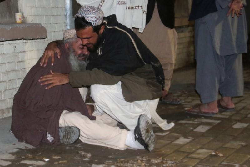 Men comfort each other as they mourn the death of a relative who was killed in a bomb blast in a mosque, at a hospital morgue in Quetta,