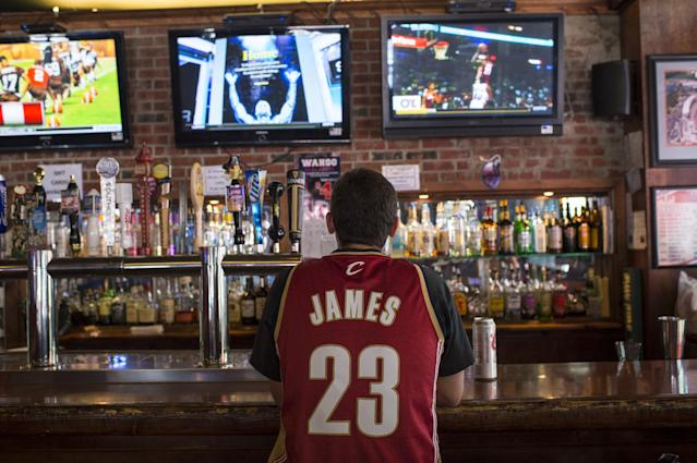 A Cleveland Cavaliers fan wearing a Lebron James jersey watches news coverage of James' return to Cleveland in downtown Cleveland, Ohio, on July 11, 2014 (AFP Photo/Angelo Merendino)