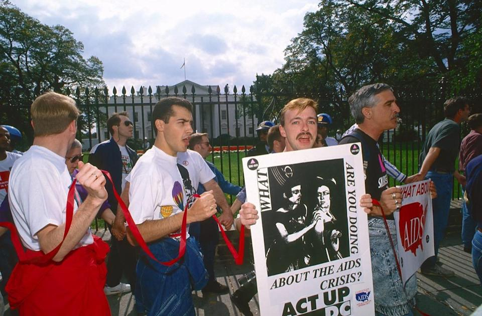 """Members of """"Act UP' and others demonstrate around the White House protesting the lack of AIDS research funding by the President George H. W. Bush administration."""