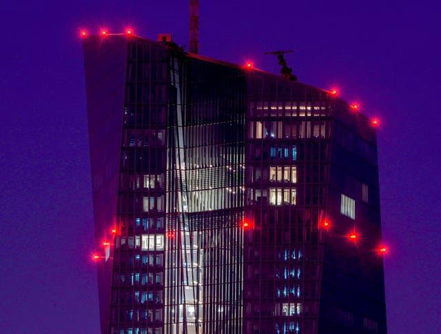 Red lights shine on top of the European Central Bank in Frankfurt (Michael Probst/AP)
