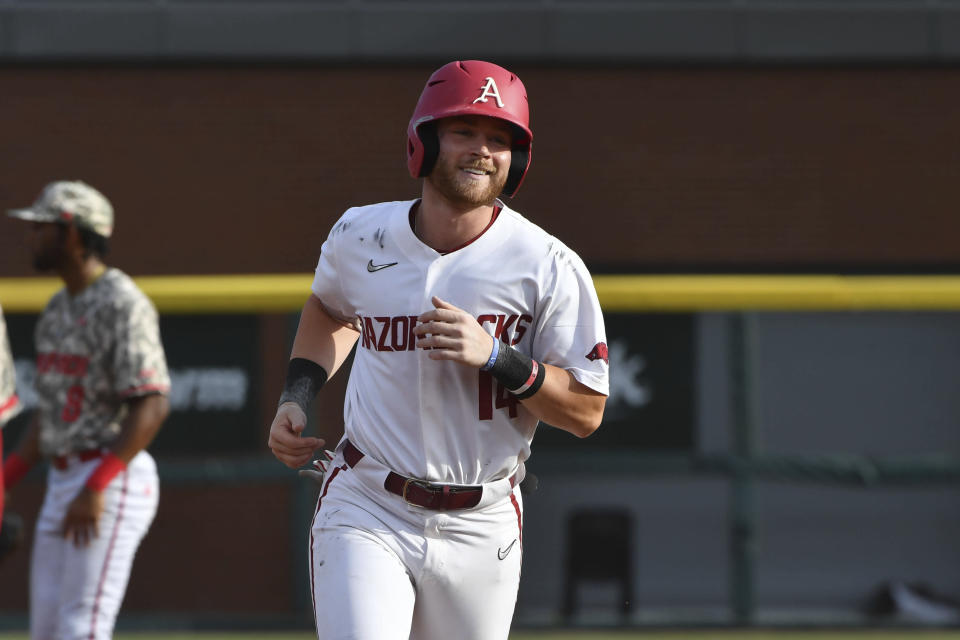 Arkansas batter Cullen Smith (14) rounds the basses after hitting a grand slam against North Carolina State in the second inning of an NCAA college baseball super regional game Friday, June 11, 2021, in Fayetteville, Ark. (AP Photo/Michael Woods)