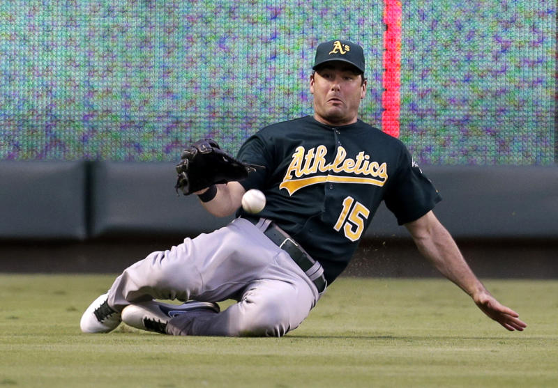 Oakland Athletics left fielder Seth Smith (15) makes a sliding grab on an RBI single by Texas Rangers' Ian Kinsler in the third inning of a baseball game Monday, June 17, 2013, in Arlington, Texas. Rangers' Leonys Martin scored on the hit. (AP Photo/Tony Gutierrez)
