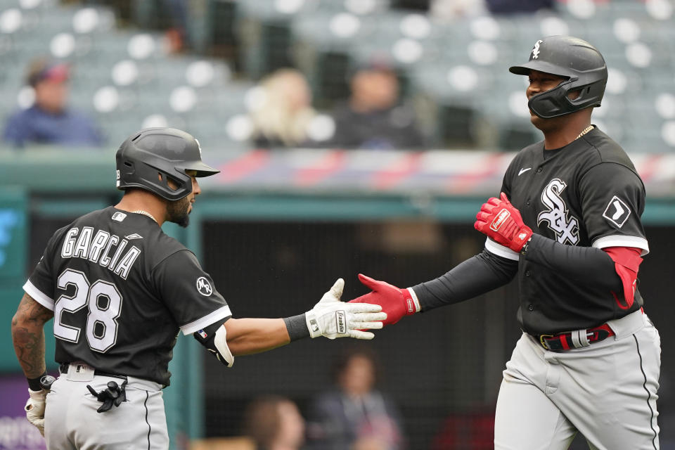 Chicago White Sox's Eloy Jimenez, right, celebrates with Leury Garcia after Jimenez hit a solo home run in the second inning in the first baseball game of a doubleheader against the Cleveland Indians, Thursday, Sept. 23, 2021, in Cleveland. (AP Photo/Tony Dejak)