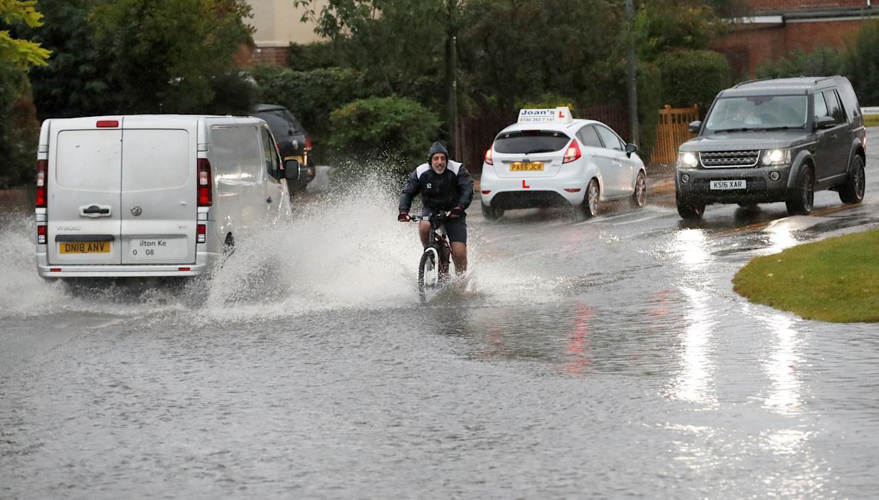 A cyclist pedals into a flooded section of road after heavy rain caused localised flooding in Milton Keynes. (Reuters)