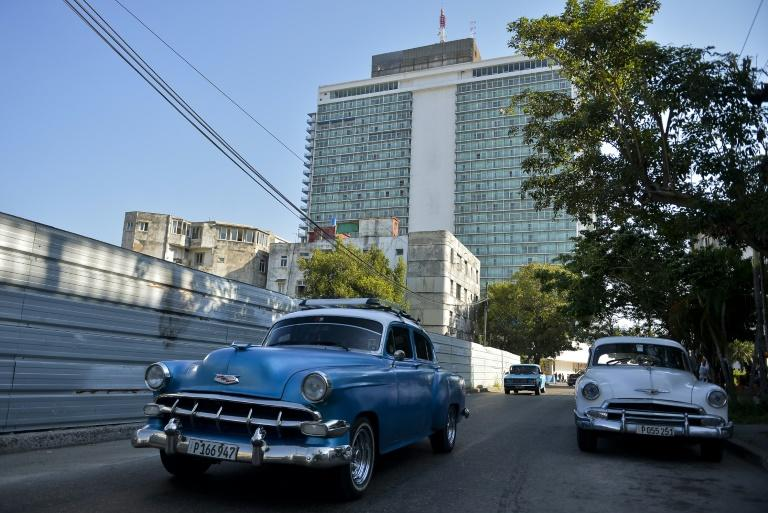 Old American cars drive near the Habana Libre Hotel in February 2019