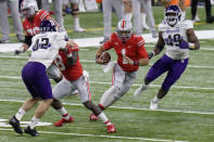 Ohio State quarterback Justin Fields (1) runs between Northwestern defenders Paddy Fisher (42) and Adetomiwa Adebawore (49) during the first half of the Big Ten championship NCAA college football game, Saturday, Dec. 19, 2020, in Indianapolis. (AP Photo/AJ Mast)
