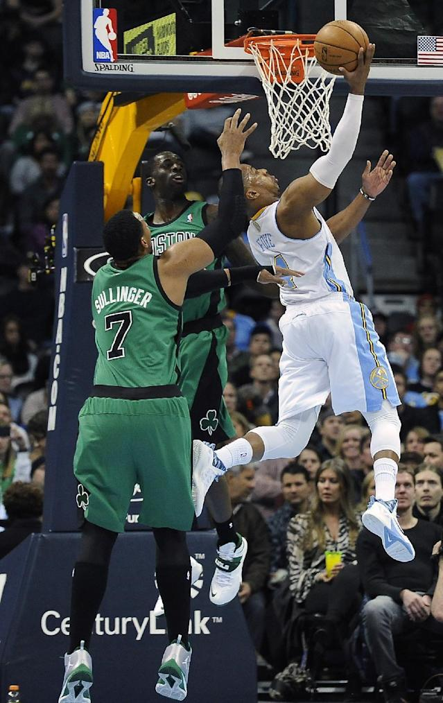 Denver Nuggets guard Randy Foye, right, scores over Boston Celtics forward Jared Sullinger, left, and Brandon Bass, center, in the first half of an NBA basketball game on Tuesday, Jan. 7, 2014, in Denver. (AP Photo/Chris Schneider)