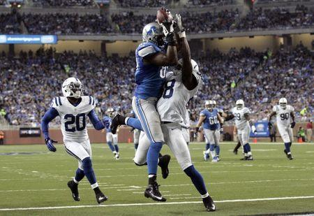 Detroit Lions tight end Brandon Pettigrew (C) completes a pass for a touch down past Indianapolis Colts Moise (R) Fokou during the first half of their NFL football game in Detroit, Michigan December 2, 2012. REUTERS/Rebecca Cook