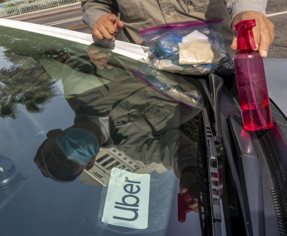 Uber driver Jose Luis Guevara, a member of the Mobile Workers Alliance, shows Personal protective equipment, PPE supplies he provides freely to ride sharing customers for their safety, outside Los Angeles City Hall, Tuesday, Jan. 12, 2021. Drivers for app-based ride-hailing and delivery services are suing to overturn a California ballot initiative that makes them independent contractors instead of employees eligible for benefits and job protections. The lawsuit filed Tuesday, Jan. 12, 2021 in the California Supreme Court said Proposition 22 is unconstitutional because it limits the power of the Legislature to grant workers the right to organize and excludes drivers from being eligible for workers' compensation. (AP Photo/Damian Dovarganes)