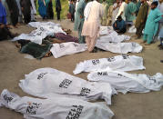 In this handout photo released by Punjab Province's Emergency Service Rescue 11222, shows people gathering around covered bodies close to the site of a deadly bus accident near Dera Ghazi Khan, Pakistan, Monday, July 19, 2021. The speeding bus carrying mostly laborers traveling home for a major Muslim holiday rammed into a container truck on a busy highway in central Pakistan, killing and injuring dozens, police and rescue officials said. (Emergency Service Rescue 1122 via AP)
