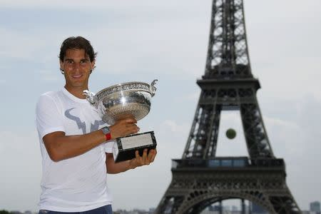Nadal of Spain poses with his trophy for photographers near the Eiffel Tower in Paris