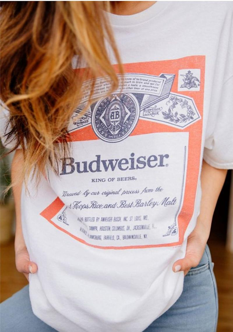 """This works as a sincere gift for the beer lover who sometimes loves to keep it simple, or as an ironic gift for the craft beer connoisseur who would never deign to touch a Bud Light. Either way, get it <a href=""""https://www.urbanoutfitters.com/en-ca/shop/junk-food-budweiser-classic-tee"""" target=""""_blank"""" rel=""""noopener noreferrer"""">at Urban Outfitters</a> for $49."""