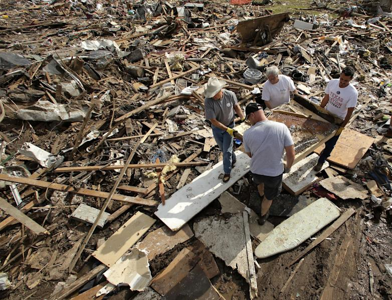 FILE - In this May 25, 2013 file photo, friends and family members carry what remains of piano through the rubble at a tornado-ravaged home, in Moore, Okla. Before construction workers can begin rebuilding the town of Moore, they have to overcome a mile-high pile of crushed wood, shattered glass, obliterated belongings and squished siding. (AP Photo/Charlie Riedel, File)