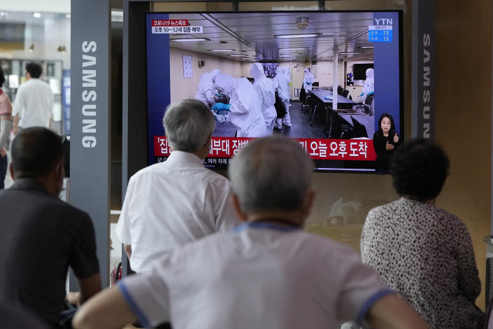 """People watch a TV showing an image of South Korean service members wearing protective clothes disinfect inside the naval destroyer Munmu the Great during a news program at the Seoul Railway Station in Seoul, South Korea, Tuesday, July 20, 2021. South Korea's prime minister on Tuesday apologized for """"failing to carefully take care of the health"""" of hundreds of sailors who contracted the coronavirus on a navy ship taking part in an anti-piracy mission off East Africa. (AP Photo/Ahn Young-joon)"""