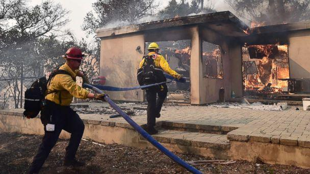 PHOTO: Firefighters knock down flames in the Point Dume neighborhood of Malibu, Calif., On Nov. 10, 2018, after the Woolsey Fire tore through the neighborhood overnight. (Robyn Beck / AFP / Getty Images)