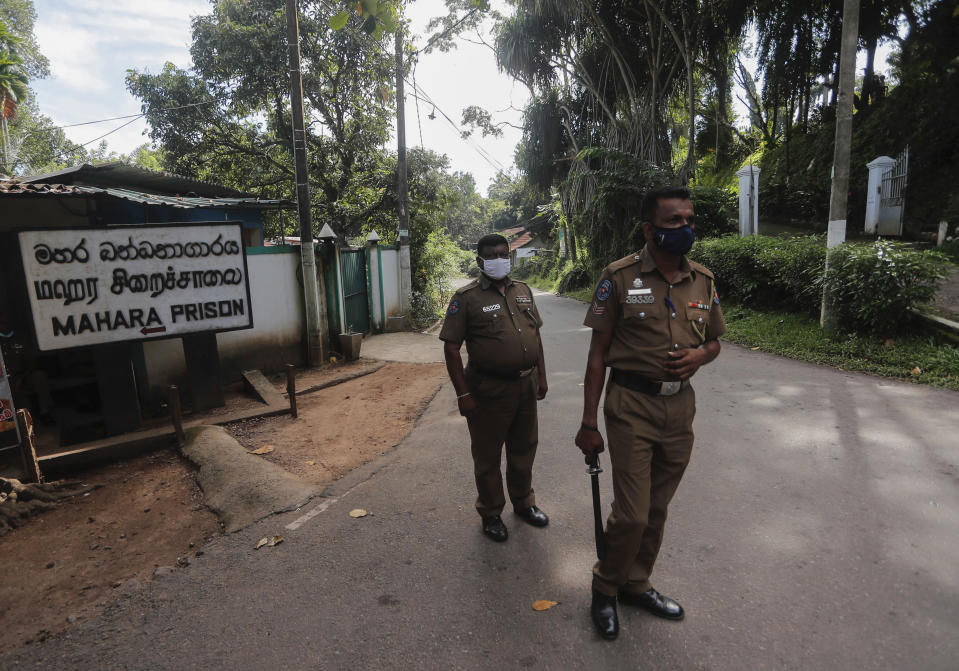 Sri Lankan police officers stand guard at the entrance to the Mahara prison complex following an overnight unrest in Mahara, outskirts of Colombo, Sri Lanka, Monday, Nov. 30, 2020. Sri Lankan officials say six inmates were killed and 35 others were injured when guards opened fire to control a riot at a prison on the outskirts of the capital. Two guards were critically injured. Pandemic-related unrest has been growing in Sri Lanka's overcrowded prisons. (AP Photo/Eranga Jayawardena)