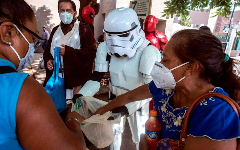 Members of the Star Wars fan club deliver food and sodas to relatives of patients hospitalised within the area of respiratory diseases at the Hospital Ignacio Garcia of the Mexican Social Security Institute - AFP