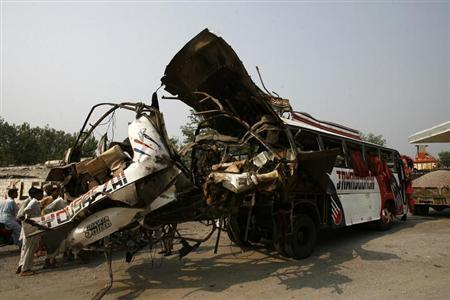 People stand near the damaged bus after it was hit by a bomb attack in the outskirts of Peshawar September 27, 2013. A bomb exploded on a bus carrying government officials in the insurgency-plagued Pakistani city of Peshawar on Friday, killing at least 17 people, including two women, officials said. REUTERS/Khuram Parvez