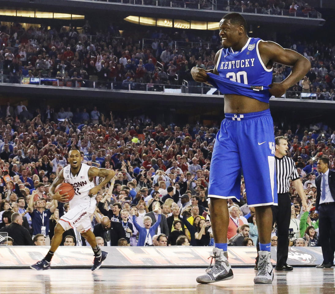 Kentucky forward Julius Randle (30) leaves the court as Connecticut guard Ryan Boatright (11) celebrates after the NCAA Final Four tournament college basketball championship game Monday, April 7, 2014, in Arlington, Texas. Connecticut won 60-54. (AP Photo/David J. Phillip)