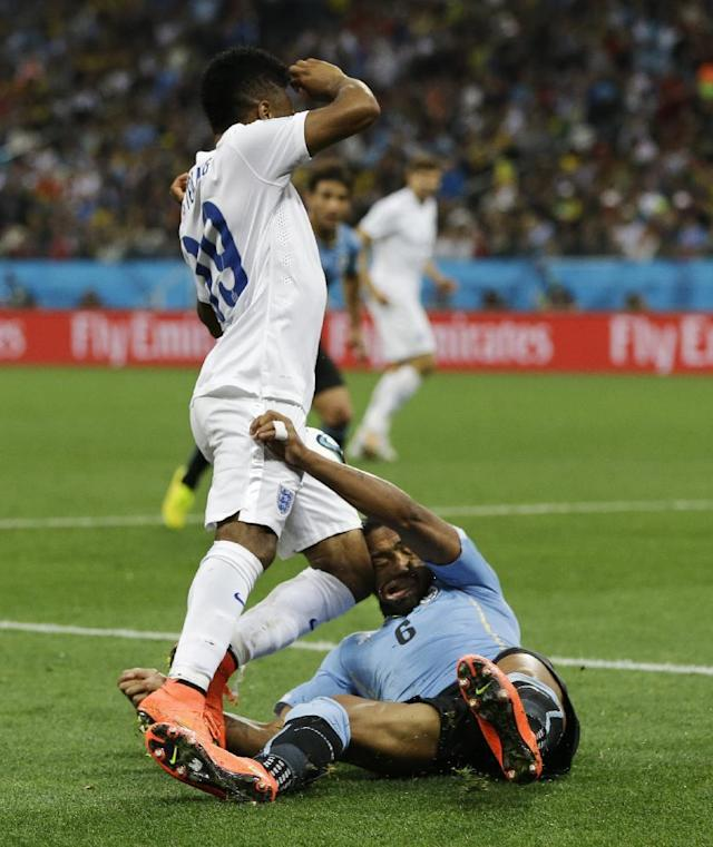 England's Raheem Sterling runs into Uruguay's Alvaro Pereira with his knee during the group D World Cup soccer match between Uruguay and England at the Itaquerao Stadium in Sao Paulo, Brazil, Thursday, June 19, 2014. Pereira was knocked out by the blow. (AP Photo/Kirsty Wigglesworth)