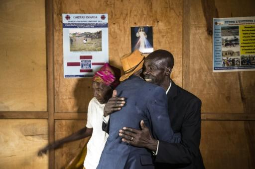 Ethnic Tutsi Jean-Bosco Gakwenzire (in the hat), 65, embraces Pascal Shyirahwamaboko, 68, who was among the killers of his father at Mutete, where the old schoolfriends have now reconciled