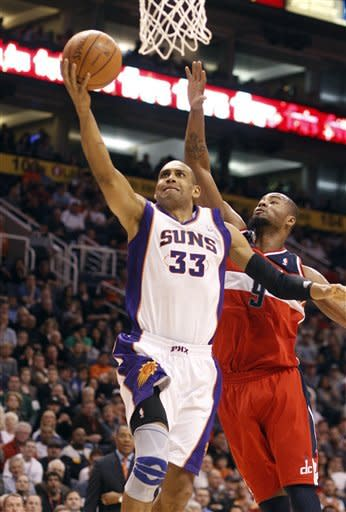 Phoenix Suns forward Grant Hill, left, lays in a basket past Washington Wizards forward Rashard Lewis during the second quarter of an NBA basketball game Monday, Feb. 20, 2012, in Phoenix. (AP Photo/Paul Connors)