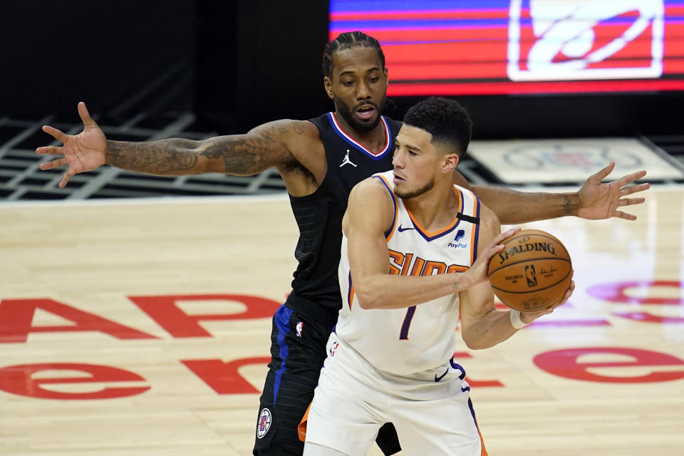 Phoenix Suns guard Devin Booker (1) holds the ball as Los Angeles Clippers forward Kawhi Leonard defends during the first half of an NBA basketball game Thursday, April 8, 2021, in Los Angeles. (AP Photo/Marcio Jose Sanchez)