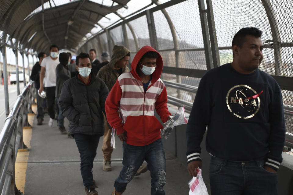 FILE - In this March 21, 2020 file photo, Central American migrants seeking asylum, some wearing protective face masks, return to Mexico via the international bridge at the U.S-Mexico border that joins Ciudad Juarez and El Paso. Vice President Mike Pence in March directed the nation's top disease control agency to use its emergency powers to effectively seal the U.S. borders, overruling the agency's scientists who said there was no evidence the action would slow the coronavirus, according to two former health officials. (AP Photo/Christian Chavez, File)